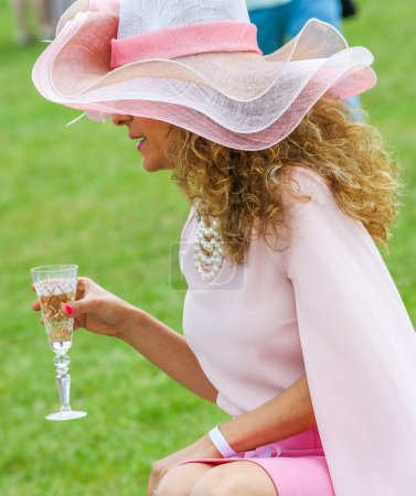 Elegant woman drinking with her beautiful hat
