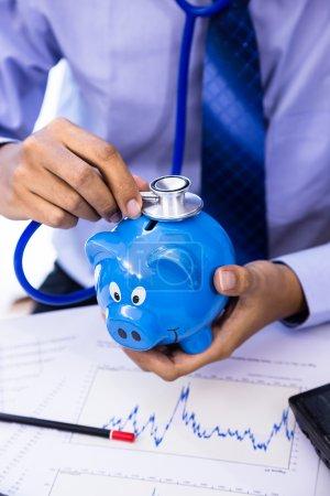 Photo pour L'homme d'affaires utilise stéthoscope avec tirelire pour le concept de bilan de santé financière - image libre de droit