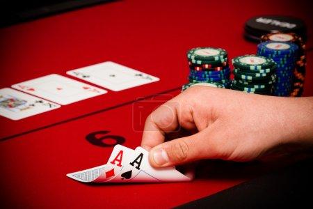 Photo pour Les mains de l'homme tenant deux cartes inutiles près une poignée de jetons, dans la pénombre, au cours d'une partie de poker - image libre de droit