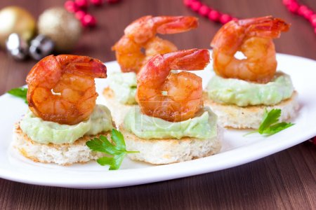 Photo for Shrimp on toast with guacamole sauce avocado, Christmas tasty elegant appetizer, starter for new year party - Royalty Free Image