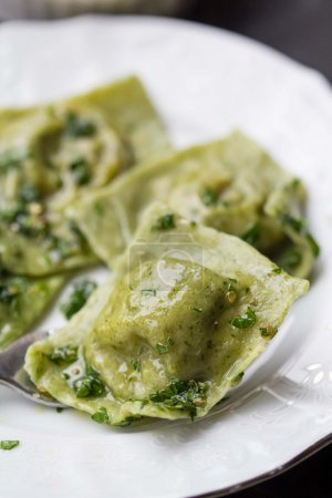 Ravioli pasta from green dough with mushroom stuffing, oil, pars