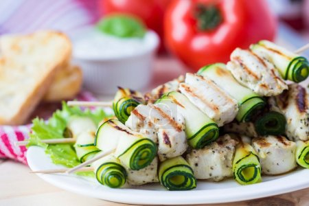 Grilled chicken kebab, shashlik on skewers with rolled zucchini,