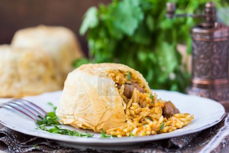 Oriental shah pilaf, pilaw, plov, rice with meat in filo
