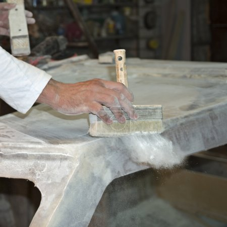 Workman hand with sweeping brush during abrading of boat surface