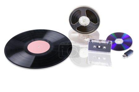 Photo pour Différents supports musicaux dans la gamme chronologique : disque de gramophone ; bobine de bande magnétique, cassette audio, disque compact, lecteur flash USB. Ils sont isolés sur du blanc . - image libre de droit