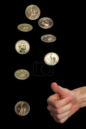 Photo for Isolated man's hand and thrown golden dollar coin in different phases of spinning. The background is black. - Royalty Free Image