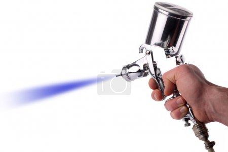 Photo pour Une main avec un pistolet de pulvérisation au travail. - image libre de droit
