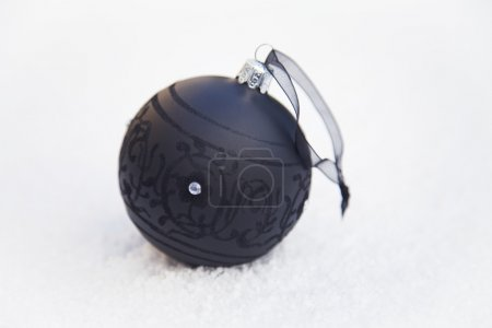 Photo for Black Christmas ball in the snow - Royalty Free Image
