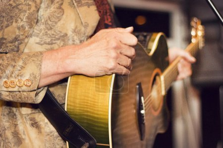 Photo for A close up of a band member playing his guitar during a party. - Royalty Free Image