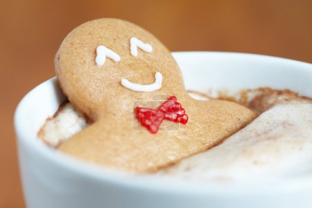 Photo for Gingerbread cookie men in a hot cup of cappuccino - Royalty Free Image
