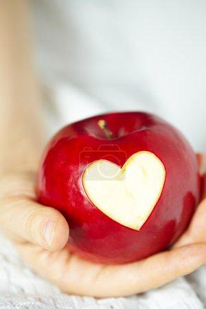 Photo pour La main de femme avec la pomme, qui a coupé un coeur - image libre de droit