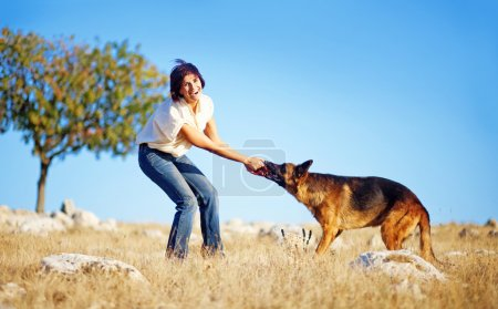 woman playing with shepherd dog