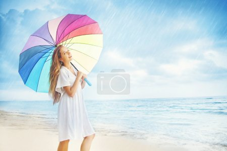 Photo for Young pretty woman with colored umbrella under the rain, bali - Royalty Free Image