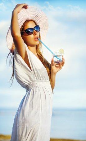 Photo pour Femme ayant reste sur la plage et profiter d'un cocktail frais d'été - image libre de droit