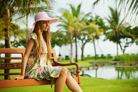 Photo for Young woman sitting on the bench in park - Royalty Free Image