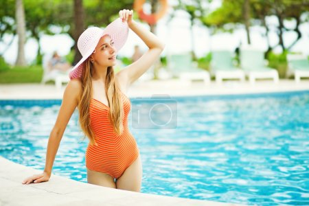 Young beautiful woman outdoors near side in swimming pool