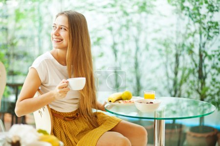 Photo for Beautiful young woman eating breakfast (soft focus) - Royalty Free Image