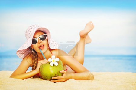 Photo for Young woman in pink swimsuit with coconut cocktail on the beach, bali - Royalty Free Image