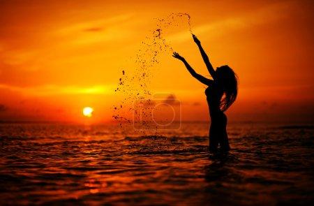 Long hair woman silhouette in the sea splashing water