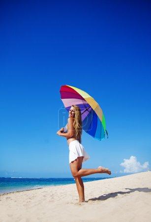 Beautiful woman with umbrella on beach, bali