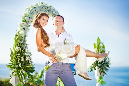 Cheerful bride and groom on the wedding venue outdoors