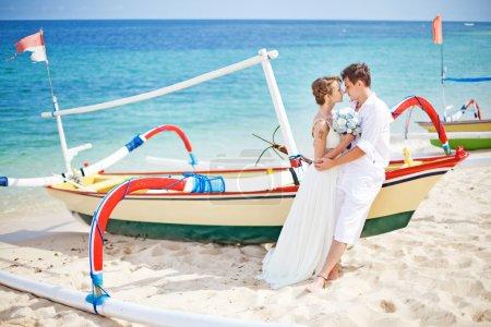 Photo pour Couple sur une plage près du bateau - image libre de droit