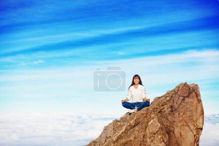 Woman doing yoga on a mountain peak