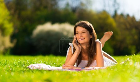 Closeup portrait of a cute young woman speaking on a mobile phone