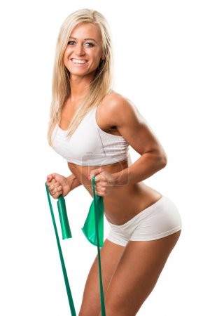 Lovely woman doing fitness exercises with rubber band.