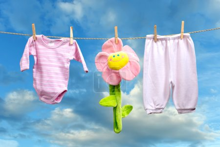 Baby girl clothes with flower on the clothesline