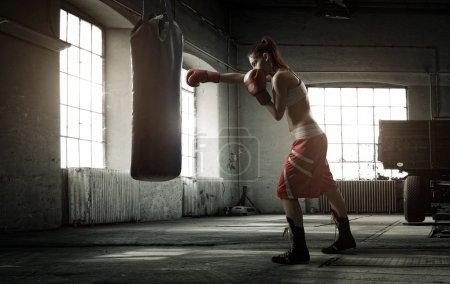 Photo pour Entraînement de boxe jeune femme dans une vieille bâtisse - image libre de droit