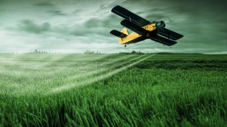 Photo for A crop dusting plane working on field - Royalty Free Image