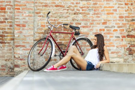 Beautiful woman with old bike