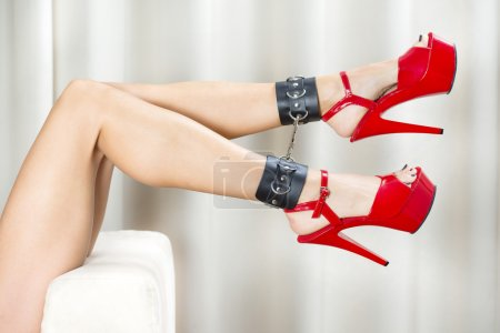 Sexy legs with ankle cuffs and red platform shoes