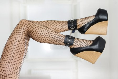 Legs in fishnet stockings, ankle cuffs and high heels