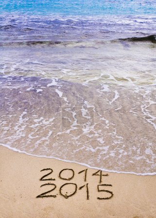 New Year 2015 is coming concept - inscription 2014 and 2015 on a beach sand, the wave is covering 2014