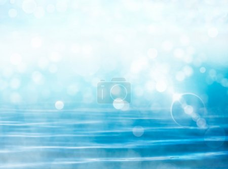 Photo for Soft focus bokeh light effects over a rippled, blue water background with lens flare. - Royalty Free Image