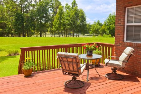 Residential backyard deck overlooking lawn and lak...