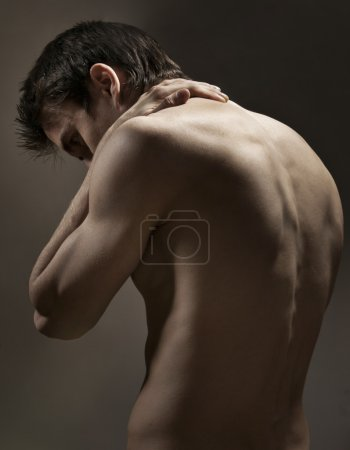 Photo for Strong athletic mans back on dark background - Royalty Free Image