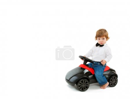 boy driving a black toy car