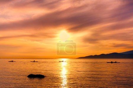 Kayakers Silhouette On Ocean During Orange Sunset