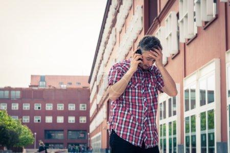 Man in short sleeve shirt talking on phone