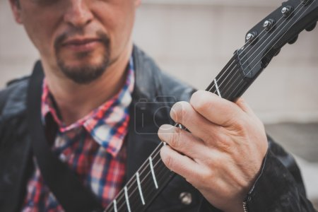 Man in black leather jacket playing electric guitar