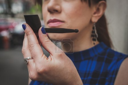 Photo pour Détail d'une jolie fille fumant pipe vintage dans la rue - image libre de droit