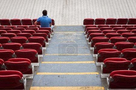Photo pour Sièges vides du stade rouge avec un homme seul - image libre de droit