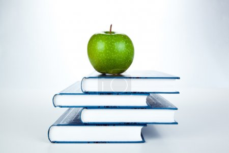 stack of books with green apple