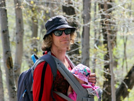 Photo pour Jeune homme avec petit bébé dans le porte-bébé dans la forêt printanière - image libre de droit