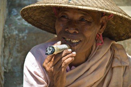 Foto de Mingun, myanmar-agosto 17: no identificada monja fumando un puro grande en mingun, cerca de mandalay, 17 agosto, 2007. un puro es un puro hecho principalmente de frutos secos y un poco de tabaco - Imagen libre de derechos