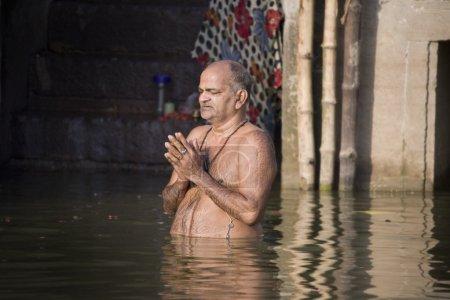 Photo pour Hindou homme en prière à Ghâts hindous sur la rive occidentale du Gange à varanasi, dans l'uttar pradesh région de l'Inde. - image libre de droit