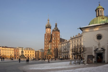 Photo for Krakow - Poland. Late afternoon in the main square (Rynek Glowny) in the old town district of Krakow in Poland. View of the Church of St. Mary, St. Adalbert's Church and the Statue of Adam Mickiewicz. - Royalty Free Image